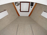 Backrest cushions become fillers to make the entire inside one large berth. There are storage shelves above the backrests.